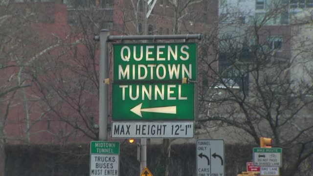 vídeos de stock, filmes e b-roll de green and white traffic sign of queens midtown tunnel entrance - tunnel