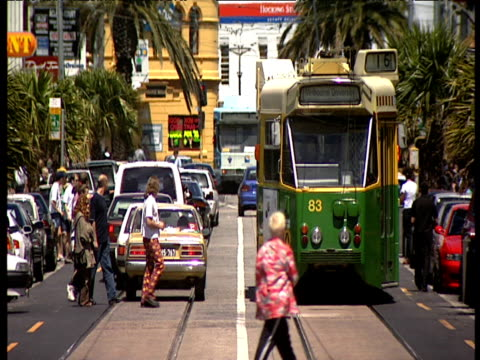 green and yellow tram approaches as people cross road avoiding busy traffic melbourne - tram stock videos & royalty-free footage