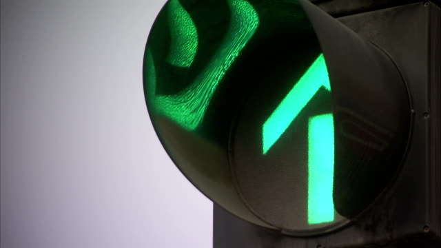 A green arrow glows on a traffic signal.