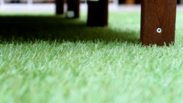 green artificial grass in indoor space/mall center with wooden furniture - zolla video stock e b–roll