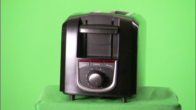 a green background surrounds a household toaster. - toaster appliance stock videos & royalty-free footage