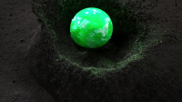 vídeos de stock e filmes b-roll de slo mo ld green ball falling into a pile of black and green dust - velocidade alta