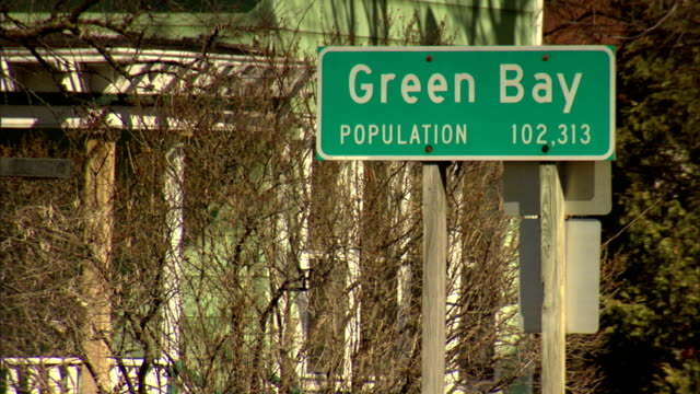 Green Bay Population 102313 sign attached to post near trees SOFT traffic moving on street FG Signage road city