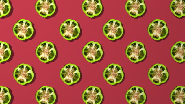 green bell pepper spinning pattern on red background - green bell pepper stock videos & royalty-free footage