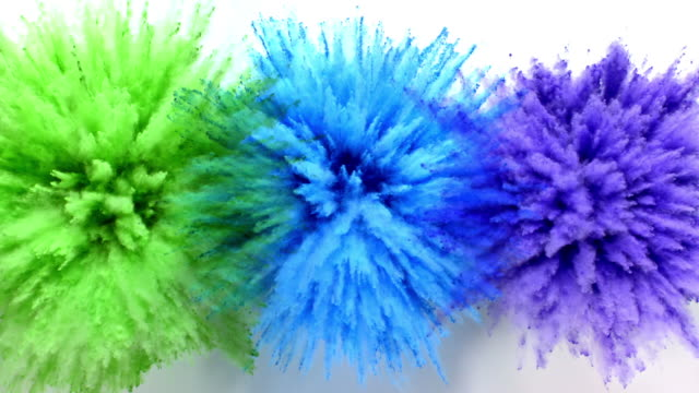 vídeos de stock e filmes b-roll de green, blue and purple colored powder exploding towards camera at the same time in a row, in close up and super slow-motion, white background - três objetos