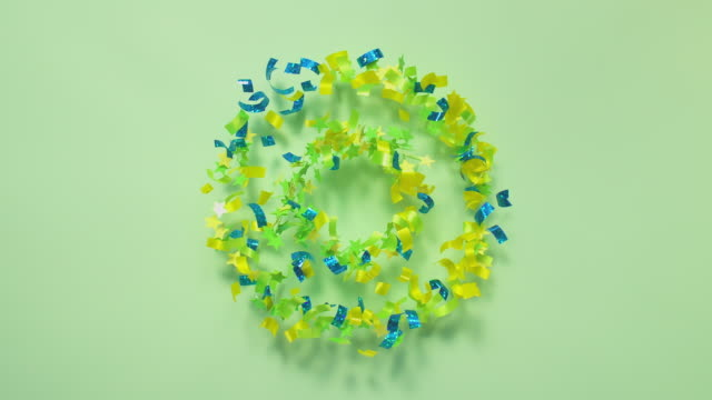 green, blue and yellow confetti and glitter exploding towards camera and becoming defocused on pastel green background, glittering bokeh - coloured background stock videos & royalty-free footage