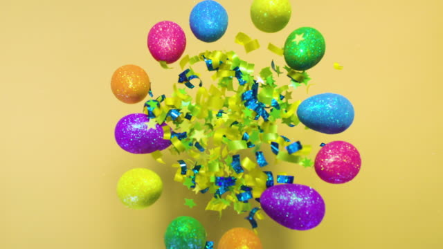 green, blue and yellow confetti surrounded by easter colorful eggs, exploding towards camera and becoming defocused on pastel yellow background - easter stock videos & royalty-free footage