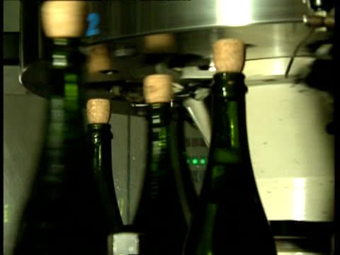 cu green bottles being corked in machine on production line, champagne - vakuum stock-videos und b-roll-filmmaterial