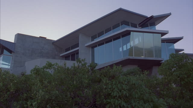 vidéos et rushes de green bushes wave in the wind beneath an upper-class, contemporary house. - moderne