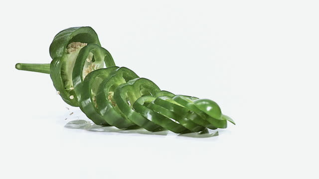 MS SLO MO Green capsicum falling on floor against white background / Vieux Pont, Normandy, France