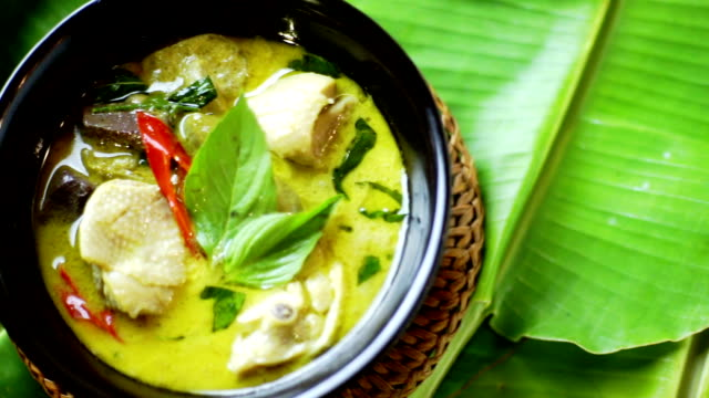 Green curry with chicken in black bowl served on banana leaf, Thai cuisine.