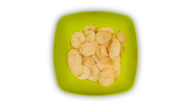 a green dish filling with ridged potato chips and emptying again, time lapse - salty snack stock videos & royalty-free footage