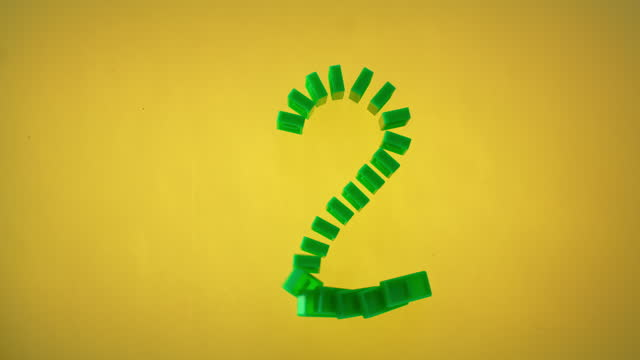 "slo mo ld green domino tiles shaped as the number ""2"" falling on yellow surface - number 2 stock videos & royalty-free footage"