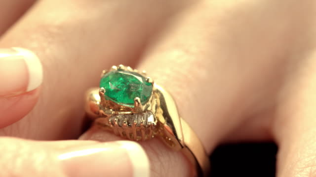 ECU green emerald stone held by setting claws in gold ring with diamonds on female hand as fingers adjust placement of ring / Los Angeles, California, USA