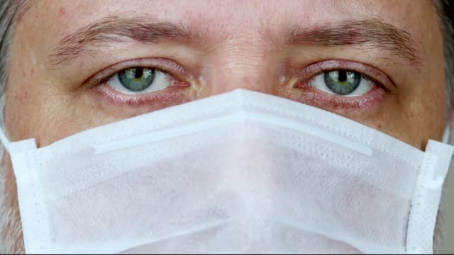 green eyed man with medical mask - blinking stock videos & royalty-free footage