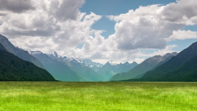 green field and mountain blue sky - horizontal stock videos & royalty-free footage