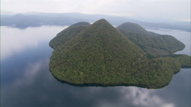 AERIAL Green, forested cone-shaped island with very steep sides in clear, smooth mountain lake / Sapporo, Hokkaido, Japan