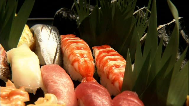 green garnishes complement a tray of nigiri sushi. - nigiri stock videos and b-roll footage