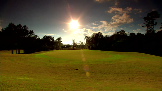green grass of fairway lined by trees, small hole in fg, sun shining brightly in center of blue sky, some clouds, golf carts moving in very distant... - putting green stock videos & royalty-free footage