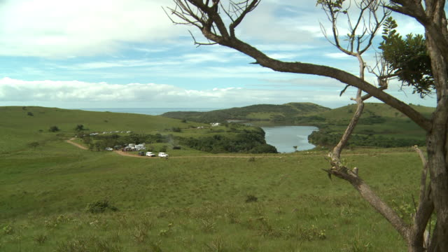 ws green grassy hills surrounding body of water dirt path road parked vans trucks white clouds in blue sky tree branches fg - kwazulu natal stock videos & royalty-free footage