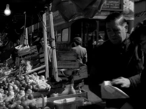 stockvideo's en b-roll-footage met a green grocer bags up some vegetables for a customer on a fruit and veg market stall 1955 - kruidenier