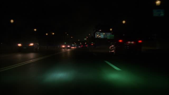 vídeos de stock e filmes b-roll de green headlights follow heavy traffic in los angeles. - 1995