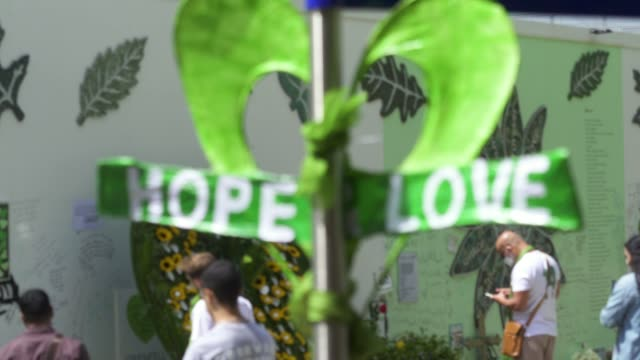 a green hear shape saying hope love next to a wall where messages of support have been written surrounding grenfell tower in west london on june 14... - shape stock videos & royalty-free footage