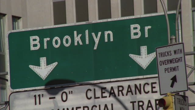 A green highway sign shows the way to the Brooklyn Bridge.