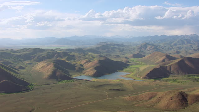 ws aerial green hills with lake and sun valley mountains in back side / idaho, united states - idaho stock videos & royalty-free footage