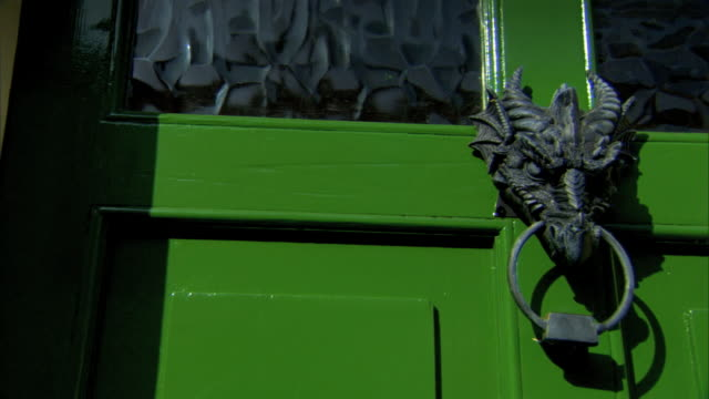 cu green house door w/ wavy glass doorknocker in shape of dragon head holding knocker as ring in mouth decorative functional - door knocker stock videos & royalty-free footage