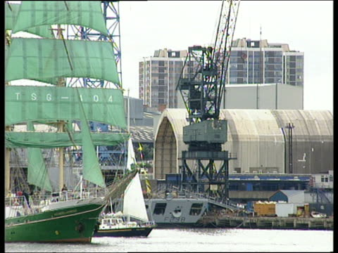 green hulled tall ship with matching sails sailing into harbour with dock buildings and cranes in background england - menschliche gliedmaßen stock-videos und b-roll-filmmaterial