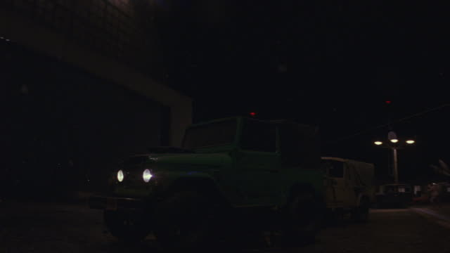 A green jeep parked in front of a building explodes into multiple pieces.
