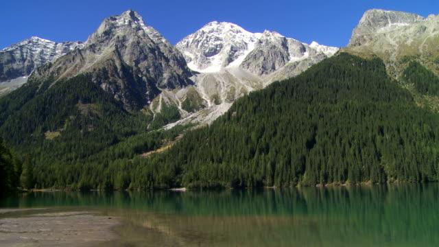 green lake in der hohe berge schwenk nach oben - gefrorenes wasser stock-videos und b-roll-filmmaterial