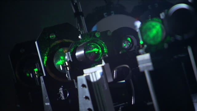 a green laser light beams through a series of lenses in starfire lab. - レーザー点の映像素材/bロール