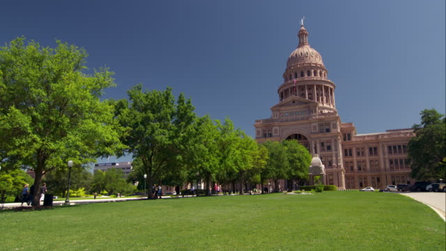 vídeos de stock, filmes e b-roll de green lawn in front of the capitol building in austin on a spring day - capitólio estatal