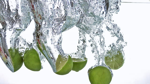 cu slo mo green lemon(citrus aurantifolia) cutted fruits entering in water / vieux pont, normandy, france - citrus fruit stock videos and b-roll footage