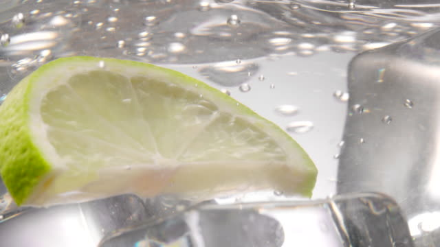 green lemon slice falling down in water with ice cubes in it - lime stock videos and b-roll footage