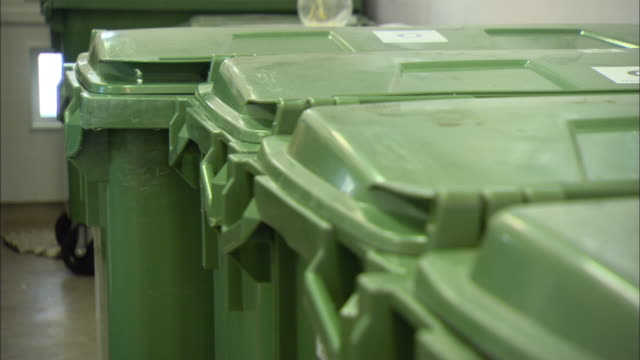 stockvideo's en b-roll-footage met cu r/f green lids of several recycling bins in recycling room / malmo, sweden - recycling