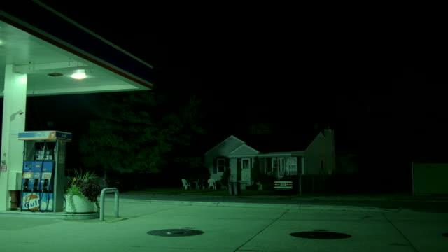 vidéos et rushes de a green light illuminates a small house near a gas station at night. - station service