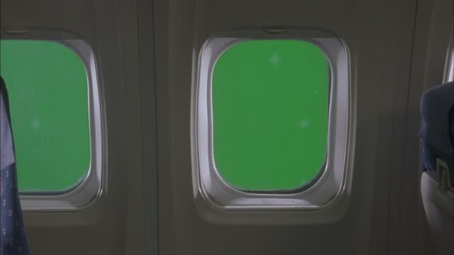 Green light shines through airplane windows.