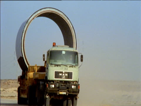 Green lorry carrying huge concrete pipe section towards and then away from camera along dusty road in desert Algeria