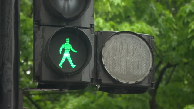 a green man crossing signal on a rainy day in london - traffic light stock videos & royalty-free footage