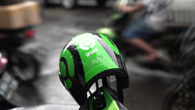 green motorcycle helmet with gojek logo hangs on a scooter in jakarta, indonesia, on tuesday, jan. 5, 2021. indonesia's ride-hailing and payments... - crash helmet stock videos & royalty-free footage
