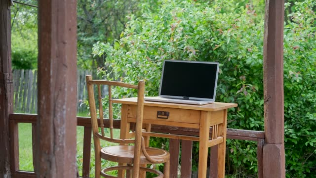 green office. business concept shot of an office desk with laptop in sunny meadow. - outdoor chair stock videos & royalty-free footage