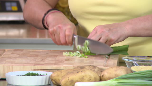 green onions. view of a woman's hands chopping green onions on a wooden board. - chopping board stock videos & royalty-free footage