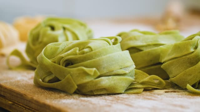 green pappardelle pasta on wooden surface - comfort food stock videos & royalty-free footage
