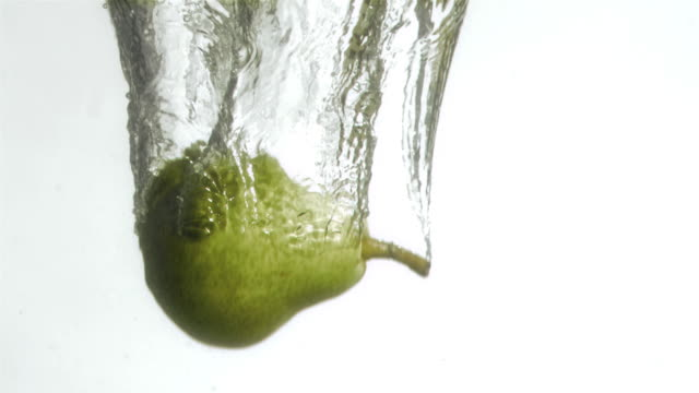 green pear in super slow motion falling in the water - pear stock videos & royalty-free footage
