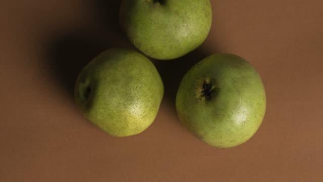 green pear over brown background - sfondo marrone video stock e b–roll