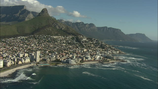 AERIAL Green Point coastline with Lion's Head, Twelve Apostles and Table Mountain in background, Cape Town, Western Cape, South Africa