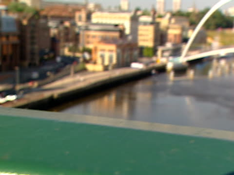 a green railing frames the gateshead millennium bridge that arches over the river tyne. - tyne and wear stock videos & royalty-free footage